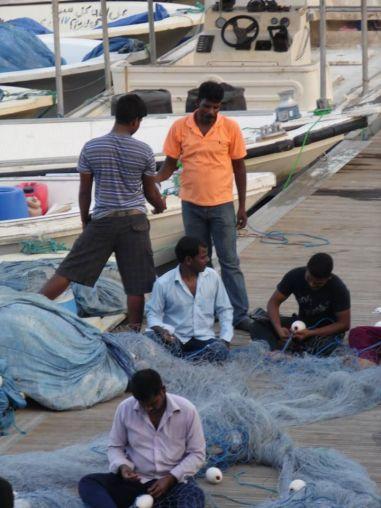 Watching skilled men fix fishing nets